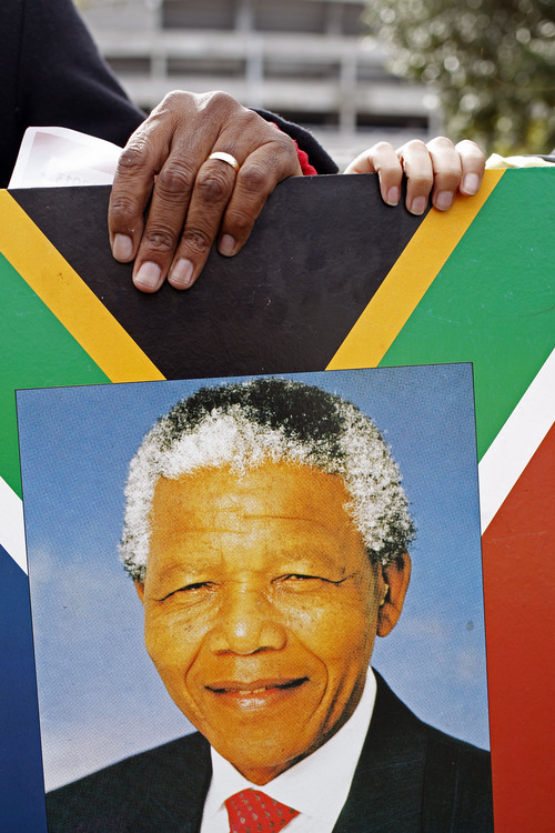 A man, left, and a woman, hold a placard with the face of former South African president Nelson Mandela as they form a human chain in celebration of his 95th birthday in Cape Town, South Africa, Thursday,  July 18, 2013.  South Africa celebrated his birthday on Thursday, a milestone capped by news that the former president's health was improving after fears that he was close to death during ongoing hospital treatment. (AP Photo/Schalk van Zuydam)