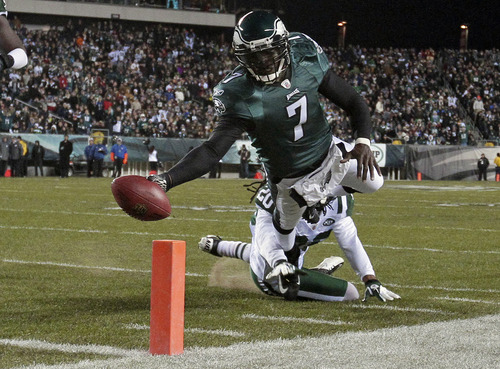 Philadelphia Eagles quarterback Michael Vick (7) scores a touchdown as New York Jets defensive back Kyle Wilson can't make the stop in the first half of an NFL football game on Sunday, Dec. 18, 2011 in Philadelphia. (AP Photo/Matt Slocum)