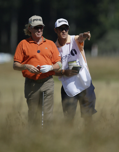 Miguel Angel Jimenez of Spain looks along the 9th fairway with his caddie Clifford Botha during the second round of the British Open Golf Championship at Muirfield, Scotland, Friday July 19, 2013. (AP Photo/Jon Super)