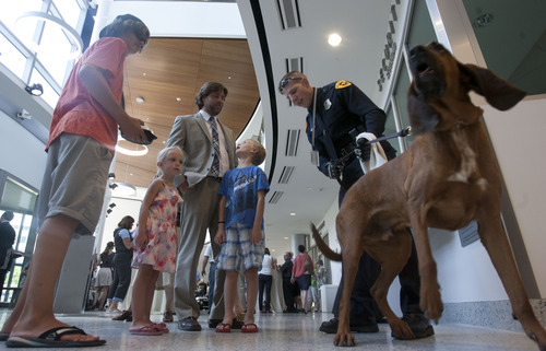 Steve Griffin | The Salt Lake Tribune  Salt Lake City police officer Tyler Lowe and partner, Chase, a single-purpose tracking bloodhound, meet the public during an open house at the new Public Safety Building in Salt Lake City Friday July 19, 2013.