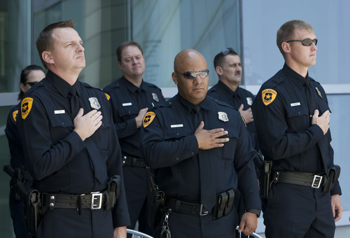 Steve Griffin | The Salt Lake Tribune  Salt Lake City police officers put their hands over their hearts during the singing of the National Anthem during a ribbon-cutting ceremony officially opening the new Public Safety Building in Salt Lake City Friday July 19, 2013.