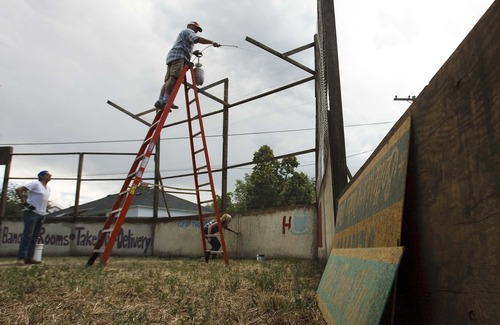 "Leah Hogsten  |  The Salt Lake Tribune l-r Chris Demuri holds a ladder for Larry Filion who paints over backstop painter Brooklyn Moore to the likeness of the original ball field from the movie ""The Sandlot"". Community members, volunteers and crew from the Utah Film Commission replicated the movie set of ""The Sandlot"" at the original site where the movie was filmed, along 1386 Glenrose Avenue, Saturday, July 13, 2013."