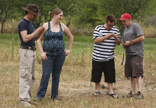 "Leah Hogsten  |  The Salt Lake Tribune l-r Devin and Melissa Barker share a laugh with their neighbor Dustin Evans who shows Utah Film Commission director Marshall Moore photos of the original ""Sandlot"", taken by his grandmother Emma Lambert whose property the ballfield was constructed. Community members, volunteers and crew from the Utah Film Commission replicated the movie set of ""The Sandlot"" at the original site where the movie was filmed, along 1386 Glenrose Avenue, Saturday, July 13, 2013."