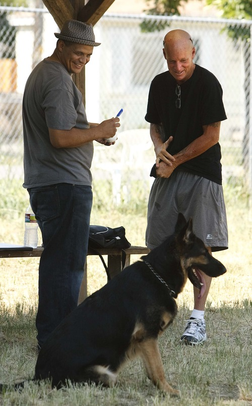 "Leah Hogsten  |  The Salt Lake Tribune The Sandlot movie screenwriter and director David M. Evans (right) shares a laugh with Billy Palmer (left) while taking a break from playing fetch with his own ""beast,"" a 3-year-old German Shepherd named Maverick, on the replicated set of ""The Sandlot"" on the original site in the neighborhood of Glendale, Utah where the movie was filmed, along 1386 Glenrose Ave., Thursday, July 18, 2013."