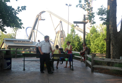 Cedar Point police standby as a person is tended to at the Shoot the Rapids ride at the Cedar Point amusement park in Sandusky, Ohio on Friday, July 19, 2013. A boat on the ride accidentally rolled backward down a hill and flipped over when the ride malfunctioned, injuring all seven people on it. (AP Photo/The Sandusky Register, Jason Werling)