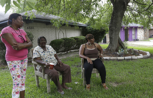 Neighbors watch from their yard as authorities investigate a home, right background, Friday July 19, 2013, in Houston where police say four homeless men were found in deplorable conditions. Officers who responded to a call expressing concern said said they found three men locked in a garage and a fourth in the home who were malnourished and may have been being held so a captor could cash checks the men were receiving. One person was taken into custody. (AP Photo/Pat Sullivan)