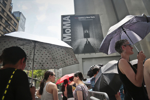 "Visitors stand in line during temperature in the 90's to experience Random International's ""Rain Room"" at the Museum of Modern Art (MoMA), an environment of falling water, Friday, July 19, 2013 in New York.  ""It's peaceful, very beautiful,"" said Lee.  Visitors wait as much as four hours to to experience a field of rain-like water that allows the individual  ""the experience of controlling the rain"" and get a reprieve from the city's heatwave in a cooler environment.  (AP Photo/Bebeto Matthews)"