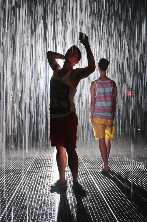 "Jin Lee, left, a student designer, and Ray Duong, right, a dental student both from New York city, experience Random International's ""Rain Room"" at the Museum of Modern Art (MoMA), wait their turn while watching others experience an environment of falling water, center, Friday, July 19, 2013 in New York.  ""It's peaceful, very beautiful,"" said Lee.  Visitors wait as much as four hours to interact  with the field of rain-like water, which pauses wherever a human body is detected, allowing visitors ""the experience of controlling the rain.""  (AP Photo/Bebeto Matthews)"