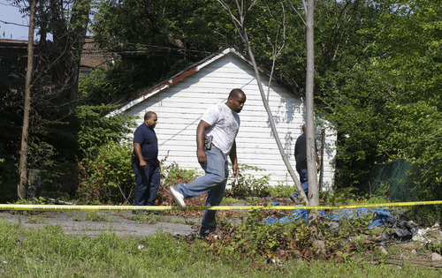 East Cleveland police search near where three bodies were recently found Sunday, July 21, 2013, in East Cleveland, Ohio. The bodies, believed to be female, were found about 100 to 200 yards (90 to 180 meters) apart, and a 35-year-old man was arrested and is a suspect in all three deaths, though he has not yet been charged, East Cleveland Mayor Gary Norton said Saturday. (AP Photo/Tony Dejak)