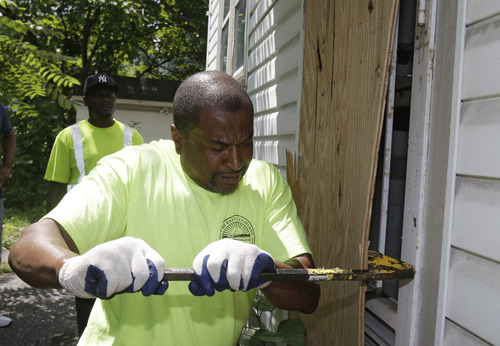 City of East Cleveland service department employee Ray Allen breaks into an abandoned house so searchers can enter Sunday, July 21, 2013, in East Cleveland, Ohio. Police Chief Ralph Spotts told volunteers checking vacant houses in a neighborhood where three bodies were found wrapped in plastic bags that he believes there could be one or two more victims. (AP Photo/Tony Dejak)