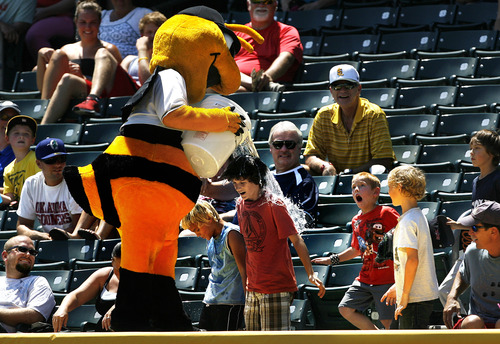 Scott Sommerdorf   |  The Salt Lake Tribune Bumble, the Bees' mascot playfully douses young fans in the stands on a day at the ballpark where the temperatures were in the high 90's, Sunday, July 21, 2013. The Bees Beat Sacramento 9-7.
