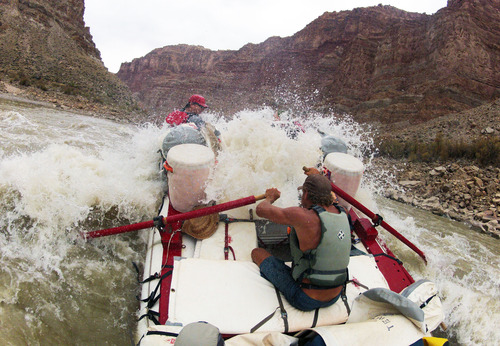 Francisco Kjolseth  |  The Salt Lake Tribune Holiday River Expeditions river guide Alex Jahp powers through a large wave while navigating the rapids in Cataract Canyon in July 2012.