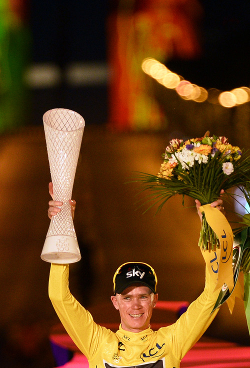 Christopher Froome of Britain, wearing the overall leader's yellow jersey, raises his cup on the podium after the 21st and last stage of the 100th edition of the Tour de France cycling race over 133.5 kilometers (83.4 miles) with start in Versailles and finish in Paris, France, Sunday July 21 2013. (AP Photo/Bernard Papon, Pool)
