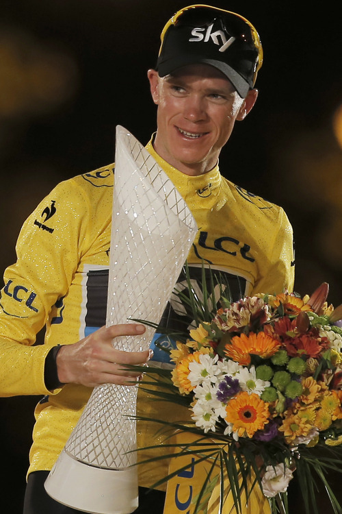 2013 Tour de France cycling race winner Christopher Froome of Britain, wearing the overall leader's yellow jersey, celebrates on the podium of the 100th edition of the Tour de France cycling in Paris, France, Sunday July 21 2013. (AP Photo/Laurent Cipriani)