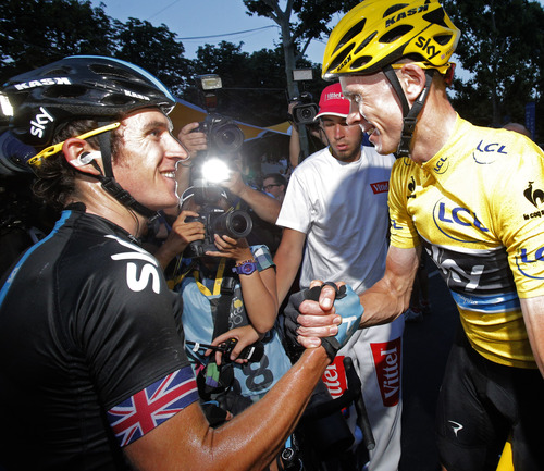 Geraint Thomas of Britain, left, congratulates teammate and 2013 Tour de France cycling race winner Christopher Froome of Britain, wearing the overall leader's yellow jersey, after the last stage of the 100th edition of the Tour de France cycling in Paris, France, Sunday July 21 2013. (AP Photo/Christophe Ena)