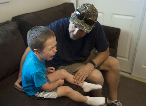 "Kim Raff  |  The Salt Lake Tribune Jason Kava soothes his son, Jason Jr., who is upset about having to put his iPad away. ""JJ"" has autism and one of Kava's goals with therapy is to minimize meltdowns."
