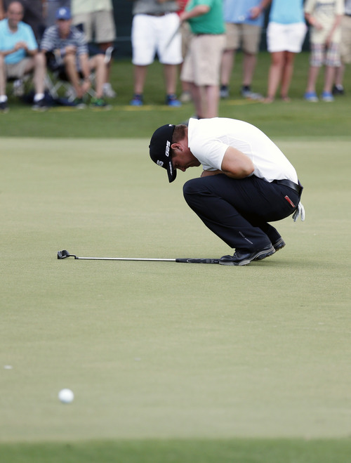 Daniel Summerhays reacts as his playoff putt lips around the hole at the Sanderson Farms Championship golf tournament on Sunday, July 21, 2013, in Madison, Miss. Woody Austin won the tournament. (AP Photo/Rogelio V. Solis)