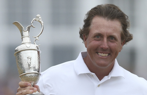 Phil Mickelson of the United States holds up the Claret Jug trophy after winning the British Open Golf Championship at Muirfield, Scotland, Sunday July 21, 2013.  (AP Photo/Scott Heppell)