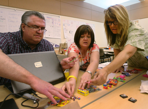 Steve Griffin  |  The Salt Lake Tribune Gordon Moses of Pleasant Grove High, Linda Brown of Desert Hills High in St. George, and Shawn Caine, of Panguitch High sort candy during a June workshop at Westminster College in Salt Lake City. Some groups grouped candy by taste, others by brand or other considerations.