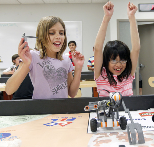 Al Hartmann  |  The Salt Lake Tribune Ariana Meinking, 11, left, and Clara Tandar, 9, cheer as their robot makes a catapault movement that they programmed at computer science summer camp hosted by the University of Utah. Some parents say it is alarming that schools don't yet offer such lessons. This summer, state education officials are taking a look at how computer-savvy Utah students should be by the time they graduate high school.