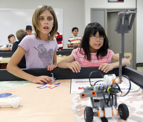 AAl Hartmann  |  The Salt Lake Tribune Ariana Meinking, 11, left, and Clara Tandar, 9, watch in anticipation as their programmable robot practices catapulting. To date, Utah students are required to show basic mastery of online and office skills before they graduate from high school. The requirements do not include robotics, graphics or programming, but state officials this summer are considering changing that.