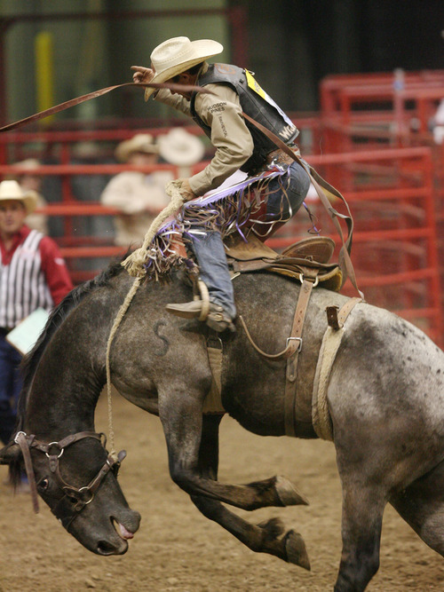 Steve Griffin | The Salt Lake Tribune   Cody Wright, of Milford, Utah, hangs on during the saddle bronc riding event at the Days of '47 Rodeo at EnergySolutions Arena in Salt Lake City, Utah Tuesday July 23, 2013.