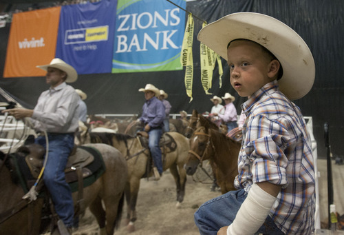 Steve Griffin | The Salt Lake Tribune   Ryder Winn, of Annabella, Utah, watches from the fence as his dad, Brian Winn, competes with Jade Anderson team robping at the Days of '47 Rodeo at EnergySolutions Arena in Salt Lake City, Utah Tuesday July 23, 2013.