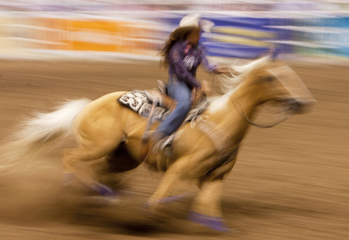 Steve Griffin | The Salt Lake Tribune   In a blur of color Brittany Pozzi, of Victoria, Texas, races around the last barrel during the barrel racing event at the Days of '47 Rodeo at EnergySolutions Arena in Salt Lake City, Utah Tuesday July 23, 2013.