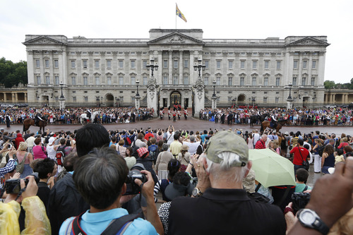 People watch the Changing of the Guard as a notice proclaiming the birth of a baby boy of Prince William and Kate, Duchess of Cambridge is put on display for the public view at Buckingham Palace in London, Tuesday, July 23, 2013. It's Day One of parenting for Prince William and Kate. After the excitement and fatigue and joy of childbirth — emotions shared with a nation — the young couple is expected to bring the prince home Tuesday. It is a daunting moment for any young couple, even one with as much support as the Duke and Duchess of Cambridge. (AP Photo/Sang Tan)