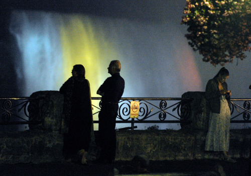 The Canadian side of Horseshoe Falls are lit up blue to celebrate the birth of the Duke and Duchess of Cambridge's son as people gather along the railing on Monday, July 22, 2013, in Niagara Falls, Canada. (AP Photo/Gary Wiepert)