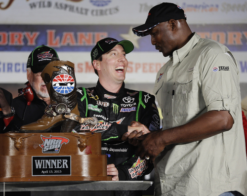 Former professional basketball player Karl Malone, right, presents the trophy after Sprint Cup Series's Kyle Busch won the NASCAR Sprint Cup series NRA 500 auto race at Texas Motor Speedway  Saturday, April 13, 2013, in Fort Worth, Texas. (AP Photo/Tony Gutierrez)