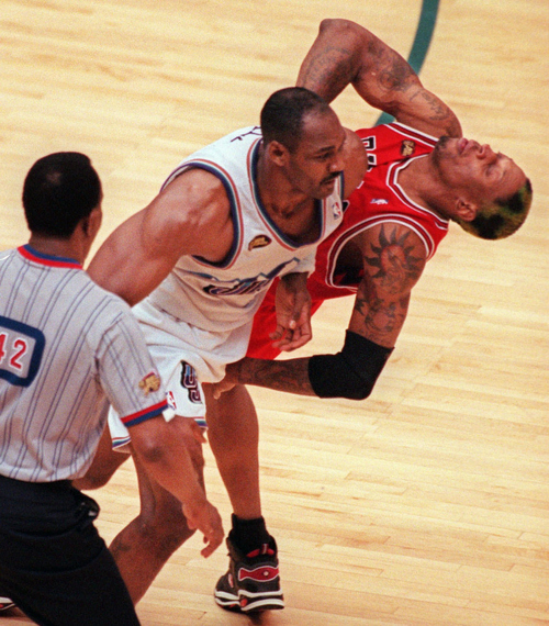 Game official Hue Hollins watches as Utah Jazz's Karl Malone, left, and  Chicago Bull's Dennis Rodman collide in the second half of Game 6 of the NBA Finals in Salt Lake City, Sunday, June 14, 1998. Rodman was called for a foul on the play.(AP Photo/Douglas C. Pizac)