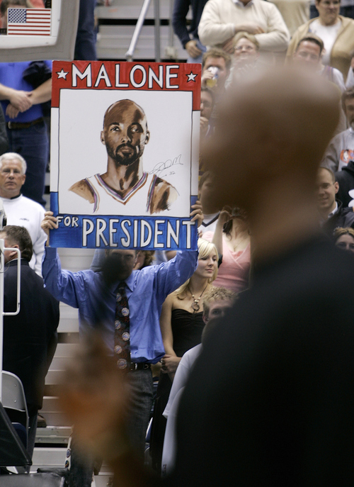 """A fan holds a """"Malone for President"""" sign as Karl Malone, foreground right, talks to the crowd at the retirement of his basketball jersey Thursday, March 23, 2006, in Salt Lake City. (AP Photo/Douglas C. Pizac)"""