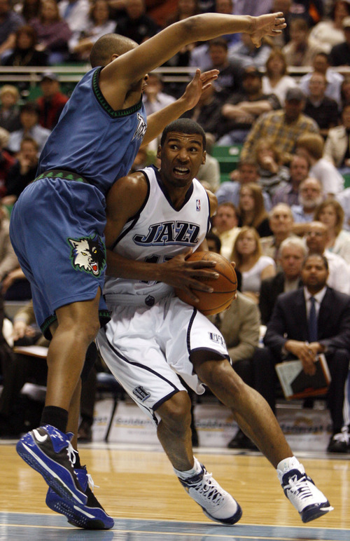 Ronnie Price drives to the basket,  under the arms of Timberwolve, Ryan Gomes in NBA action Jazz vs. the Minnesota Timberwolves at EnergySolutions Arena Wednesday, March 5,  2008   Rick Egan/The Salt Lake Tribune 3/5/08