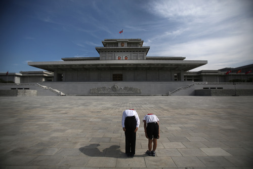 Two North Korean schoolchildren bow and pay respects to their late leaders Kim Il Sung and Kim Jong Il whose bodies lie embalmed in the mausoleum, the Kumsusan Palace of the Sun, on Thursday, July 25, 2013 in Pyongyang, North Korea. (AP Photo/Wong Maye-E)