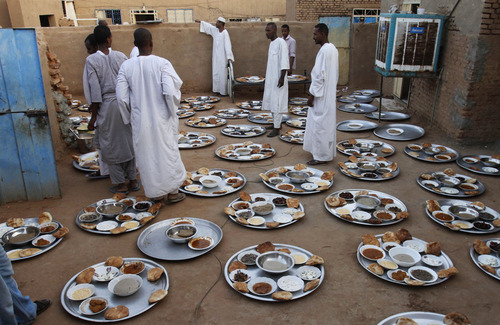 In this Wednesday, July 24, 2013 photo, Sudanese Muslims from the Qadiriyah Sufi order, prepare food for 'Iftar' during the holy month of Ramadan, in Kabashi, north Khartoum, Sudan. Ramadan is the holiest month in Islam and observant Muslims worldwide mark it by fasting from dawn to dusk. (AP Photo/Abd Raouf)
