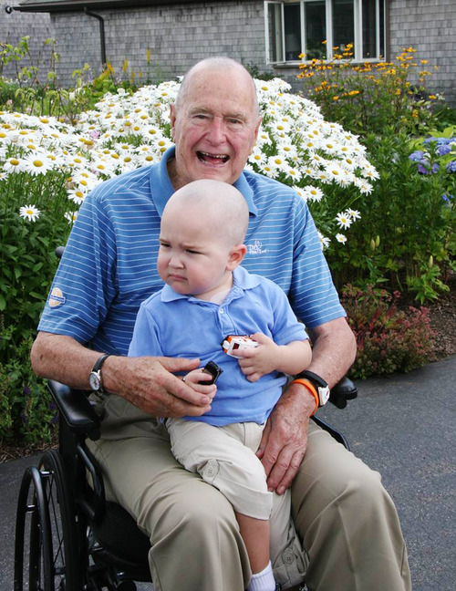 This Wednesday July 24, 2013 photo provided by the Office of George Bush shows President George H. W. Bush with Patrick (last name withheld at family's request), 2, in Kennebunkport, Maine. Bush this week joined members of his Secret Service detail in shaving his head to show solidarity for Patrick, who is the son of one of the agents. The child is undergoing treatment for leukemia and is losing his hair as a result. (AP Photo/Office of George Bush)