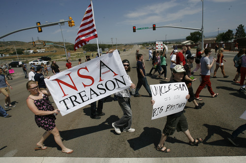Francisco Kjolseth     The Salt Lake Tribune Brandon Otterstron, center, of Clearfield joins others to protest the new NSA Data Center along Redwood road across from Camp Williams on the 4th of July.