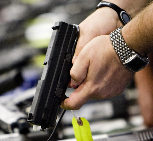 Tribune file photo Someone attending a Utah gun show in 2011 grips a pistol. Utah will revoke the concealed weapons permit of anyone who has a medical marijuana license.