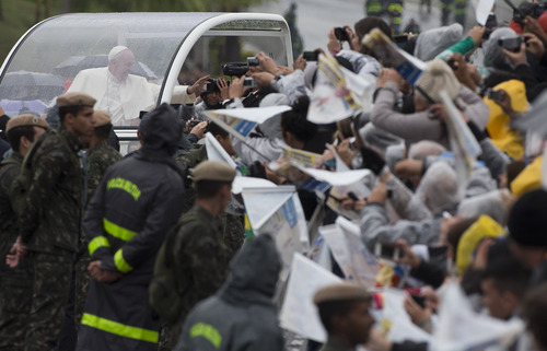 Pope Francis greets pilgrims from his popemobile as he arrives to the Aparecida Basilica in Aparecida, Brazil, Wednesday, July 24, 2013.  Tens of thousands of faithful flocked to the tiny town of Aparecida, tucked into an agricultural region halfway between Rio de Janeiro and Sao Paulo, where he is to celebrate the first public Mass of his trip in a massive basilica dedicated to the nation's patron saint. (AP Photo/Domenico Stinellis)