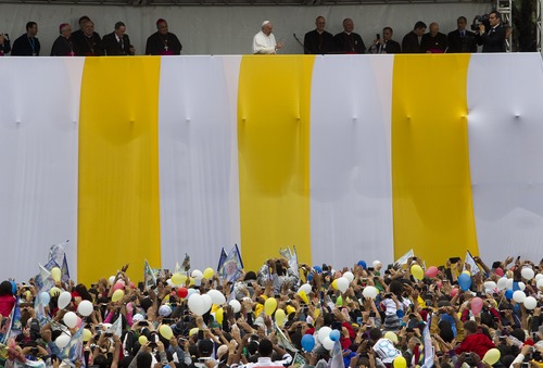 Pope Francis, top center, waves to the crowd in the Varginha slum in Rio de Janeiro, Thursday, July 25, 2013. Francis on Thursday visited one of Rio de Janeiro's shantytowns, or favelas, a place that saw such rough violence in the past that it's known by locals as the Gaza Strip.  (AP Photo/Domenico Stinellis)