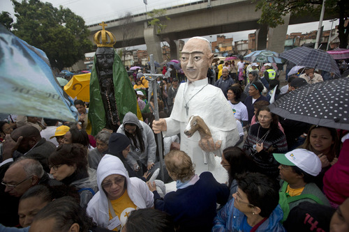 Large puppets that resemble Pope Francis, right, and the Virgin of Aparecida, Brazil's patron saint, stand tall among residents waiting for Pope Francis' arrival to the Varginha slum Rio de Janeiro, Brazil, Thursday, July 25, 2013. Pope Francis will bless the Olympic flag, visit this slum and address young Roman Catholics in Rio de Janeiro's Copacabana beach on Thursday, as Latin America's first pope continues his inaugural international trip as pontiff. (AP Photo/Victor R. Caivano)