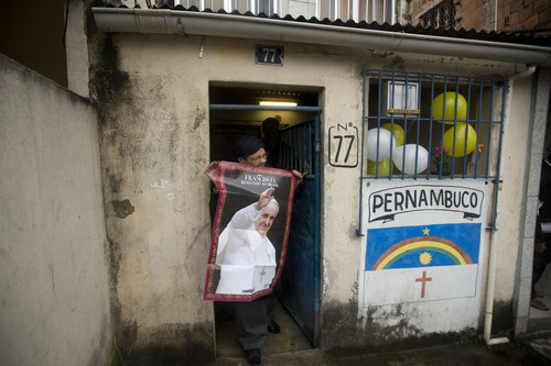 """A woman poses with a poster of Pope Francis outside her home before the Pope's arrival in the Varginha slum in Rio de Janeiro, Brazil, Thursday, July 25, 2013. The writing on the wall reads """"Pernambuco,"""" one of Brazil's states. Pope Francis will bless the Olympic flag, visit this slum and address upward of 1 million young Roman Catholics in Rio de Janeiro's Copacabana beach on Thursday, as Latin America's first pope continued his inaugural international trip as pontiff. (AP Photo/Victor R. Caivano)"""