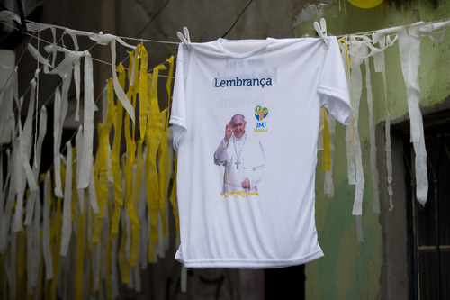 """A T-shirt showing Pope Francis that reads in Portuguese """"Souvenir"""" hangs along with streamers decorating the Varginha slum before Pope Francis' arrival in Rio de Janeiro, Brazil, Thursday, July 25, 2013. Pope Francis will bless the Olympic flag, visit this slum and address upward of 1 million young Roman Catholics in Rio de Janeiro's Copacabana beach on Thursday, as Latin America's first pope continued his inaugural international trip as pontiff. (AP Photo/Victor R. Caivano)"""