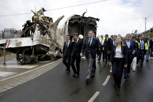 Spain's Prime Minister Mariano Rajoy, center, walks with Spain's Public Works Minister Ana Pastor, right and the President of Galicia Alberto Nunez Feijoo, second from left at the scene of a train crash in Santiago de Compostela, Spain, Thursday July 25, 2013. A Spanish train that hurtled off the rails and smashed into a security wall as it rounded a bend was going so fast that carriages tumbled off the tracks like dominos, killing 80 people, according to eyewitness accounts and video footage obtained Thursday. An Associated Press analysis of video images suggests that the train may have been traveling at twice the speed limit for that stretch of track. (AP Photo/Emilio Lavandeira, Pool)