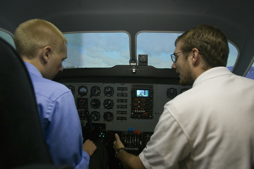 Rick Egan  | The Salt Lake Tribune   Student Tyler Gaebe, (left) gets instructions from flight Instructor Mike Manning (right) while sitting in a flight simulator at Westminster College, Thursday, July 25, 2013.