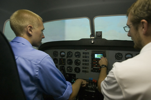 Rick Egan  | The Salt Lake Tribune  Student Tyler Gaebe, left, gets instructions from flight Instructor Mike Manning, right, while sitting in a flight simulator at Westminster College, Thursday, July 25, 2013.