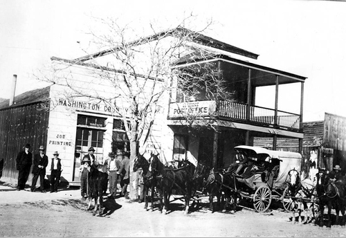 Photo Courtesy Utah State Historical Society  William Perry Stage Coach outside of Post Office and the printing office, the Modena was the St. George daily. The stage would arrive at St. George at 8:00 p.m. and leave at 2:00 a.m.