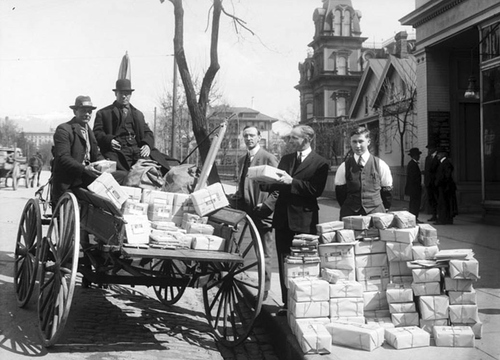 Photo Courtesy Utah State Historical Society  Image shows several men loading the contents of a large postal delivery into a wagon. The Gardo House can be seen in the background, 1914.