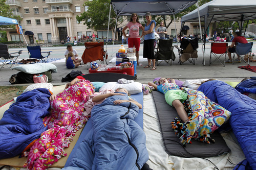 Al Hartmann  |  The Salt Lake Tribune Children of the extended Owen family, which has made it a family tradition to camp out along the front spots of the Days of '47 Parade route along Soputh Temple, catch some much-needed sleep before the parade begins. They have been doing this for over 30 years.